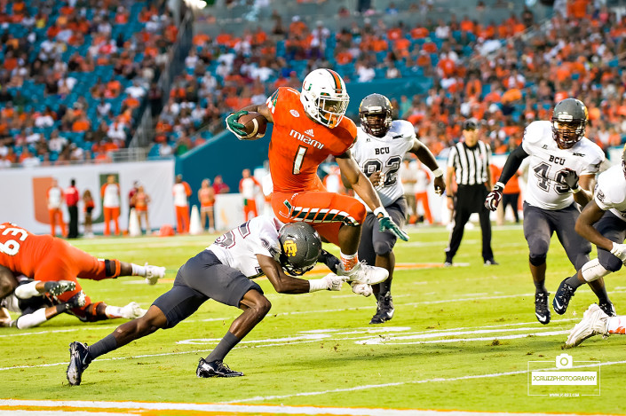 mark walton leaps over a defender