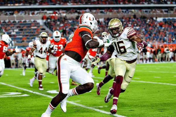 Hurricanes TE, David Njoku, extends a stiff arm on Florida State LB, Jacob Pugh