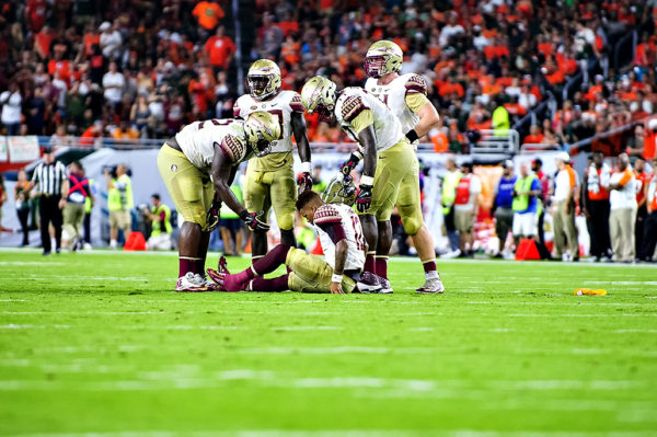Deondre Francois, Florida State QB, sits on the ground after a hit from the Miami defense