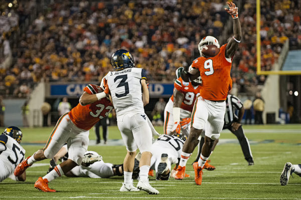 Miami Hurricanes DL, Chad Thomas, deflects a pass from West Virginia QB, Sklyer Howard