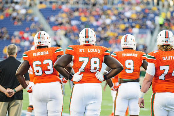 Miami Hurricane players watch their teammates battle in warmups