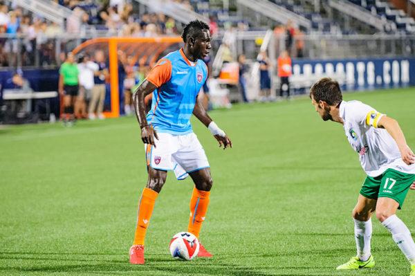 Miami FC midfielder, Kwadwo Poku, tires to dribble past a defender