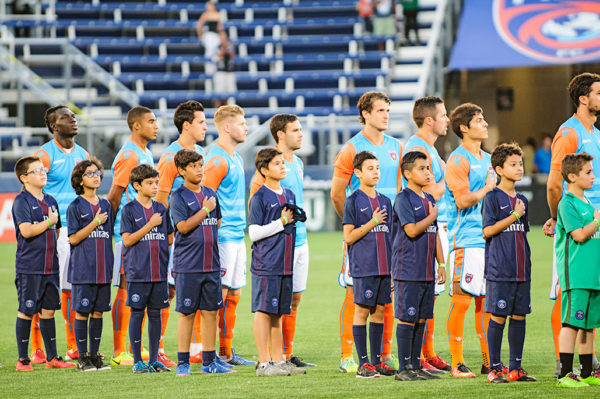 Miami FC players stand for the National Anthem