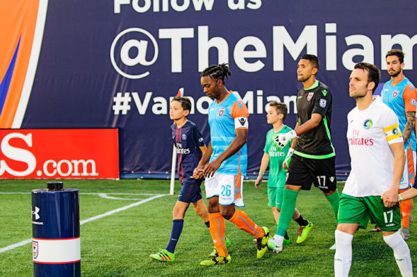 Players walk out with kids prior to the match