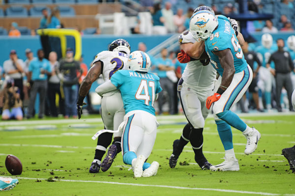 Dolphins CB #41, Byron Maxwell, forces Ravens RB #28, Terrance West, to fumble the ball