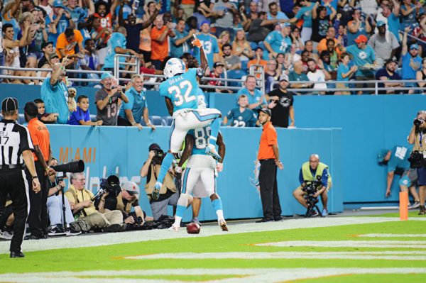 Dolphins RB, #32 Kenyan Drake, jumps on the back of TE, Leonte Carroo, after Carroo scored a touchdown