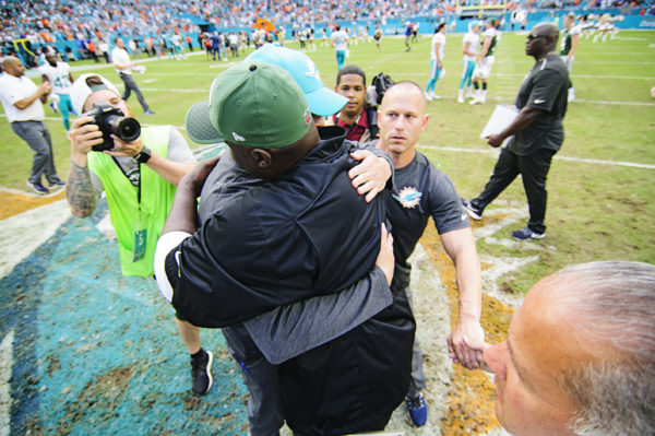 Adam Gase and Todd Bowles hug after the game