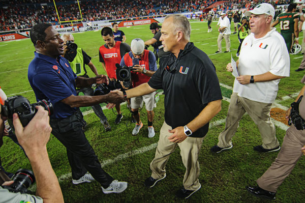 Coaches exchange handshakes after the game