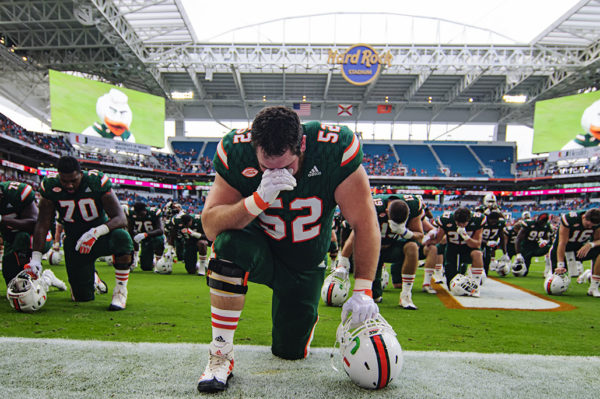 The Hurricane players take a knee prior to the game