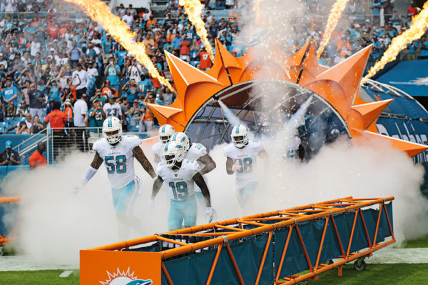 Dolphin players run through smoke and fire