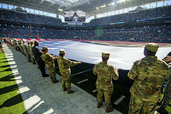 The American flag covers the entire field during the National Anthem