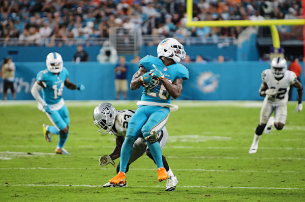 Damien Williams (26) tries to spin out of a tackle