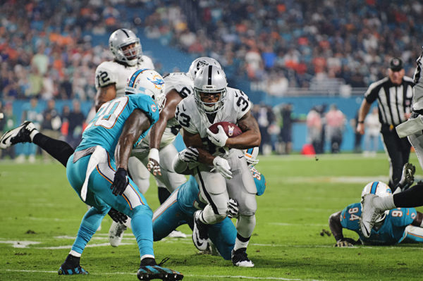 DeAndre Washington (33) tries to run past the Dolphin defenders