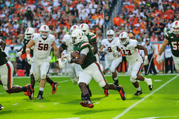 DeeJay Dallas (13) runs after taking the hand off