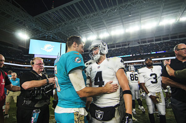 Jay Cutler (6) and Derek Carr (4) talk to one another after the game