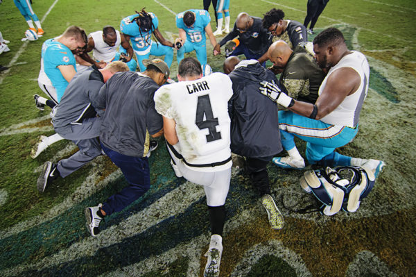 Players gather at the 50 yard line for a prayer