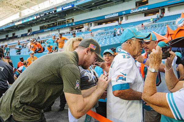 Dolphins Quarterback Ryan Tannehill signs a jersey before the game