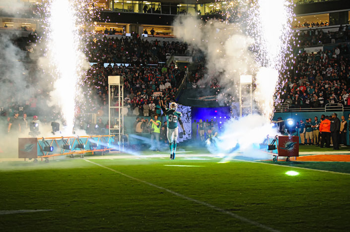 Kenyan Drake points to the sky as fireworks go off behind him