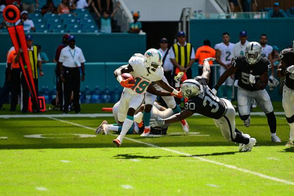 Miami Dolphins wide receiver Jakeem Grant (19) stiff arms Oakland Raiders running back Jalen Richard (30)