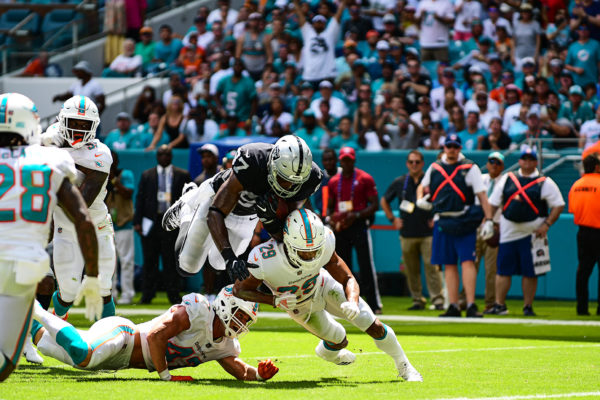 Oakland Raiders tight end Jared Cook (87) tries to leap over Miami Dolphins defensive back Minkah Fitzpatrick (29) and Miami Dolphins linebacker Kiko Alonso (47)