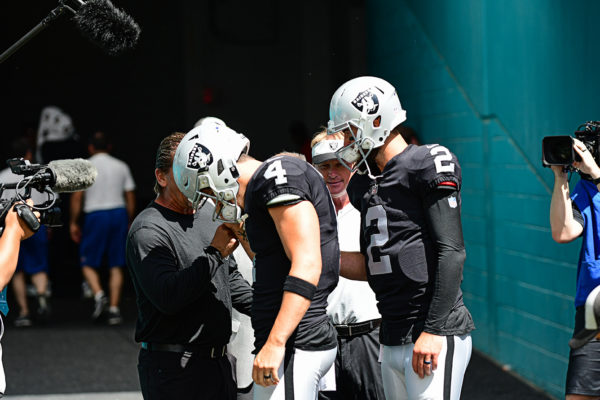 Oakland QBs have a quick little huddle before running onto the field