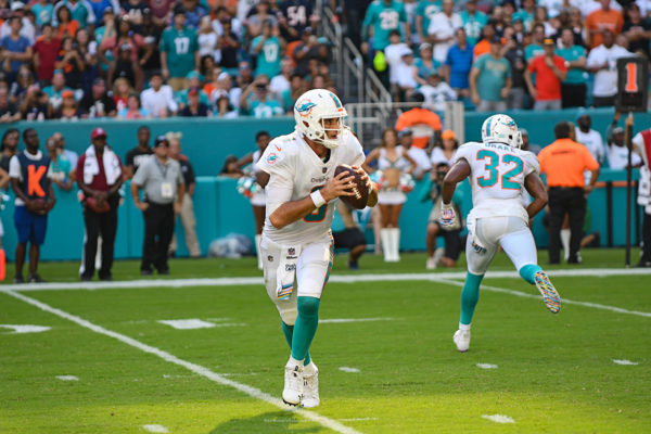 Miami Dolphins quarterback Brock Osweiler (8) rolls out of the pocket