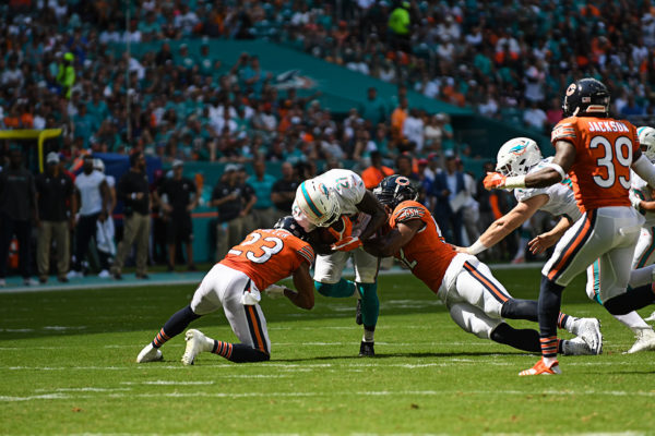 Miami Dolphins running back Frank Gore (21) gets tackled by Chicago Bears outside linebacker Khalil Mack (52) and Chicago Bears cornerback Kyle Fuller (23)