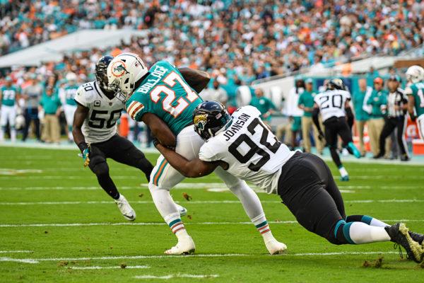 Jacksonville Jaguars defensive end Lyndon Johnson (92) tackles Miami Dolphins running back Kalen Ballage (27) for a loss