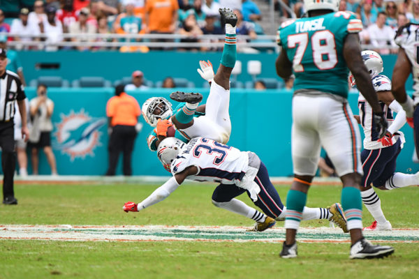 New England Patriots free safety Devin McCourty (32) tackles Miami Dolphins running back Frank Gore (21)