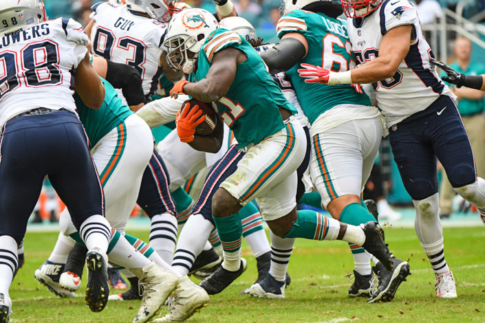 Miami Dolphins running back Frank Gore (21) tries to find a hole to run through