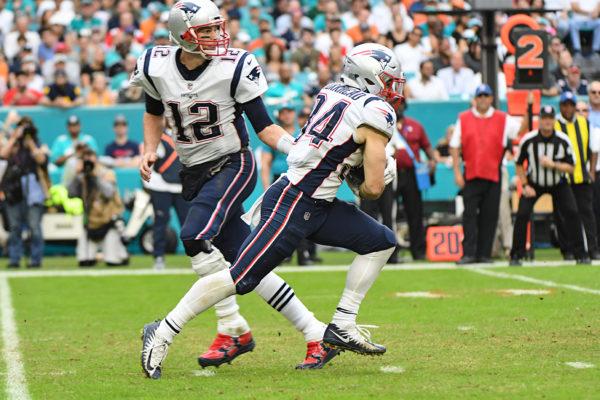 New England Patriots quarterback Tom Brady (12) hands off to New England Patriots running back Rex Burkhead (34)