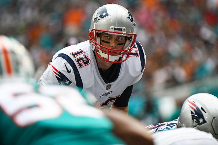 New England Patriots quarterback Tom Brady (12) looks at the defender