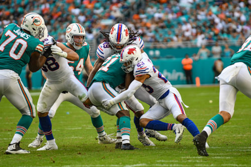 Miami Dolphins running back Frank Gore (21) is tackled by Buffalo Bills middle linebacker Tremaine Edmunds (49) and Buffalo Bills strong safety Micah Hyde (23)