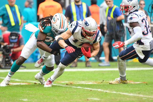 Miami Dolphins defensive back Walt Aikens (35) tackles New England Patriots wide receiver Julian Edelman (11)