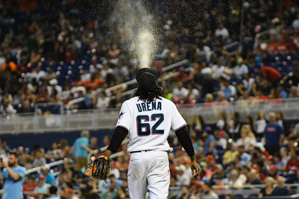 Miami Marlins starting pitcher Jose Urena (62) spits water into the air as he walks to the mound