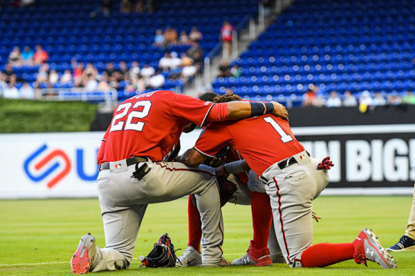 Washington Nationals players kneel for a prayer before the game