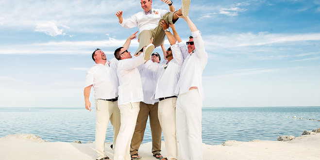 The groomsmen hoisting the groom into air